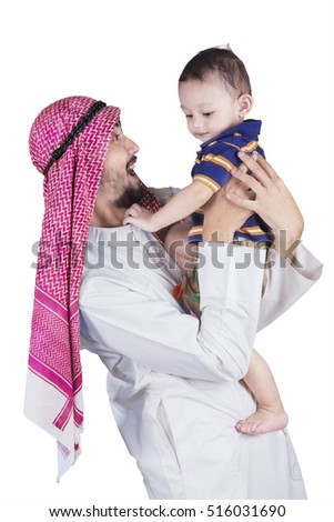 Happy arabian man wearing islamic clothes laughing with his cute boy in the studio, isolated on white background