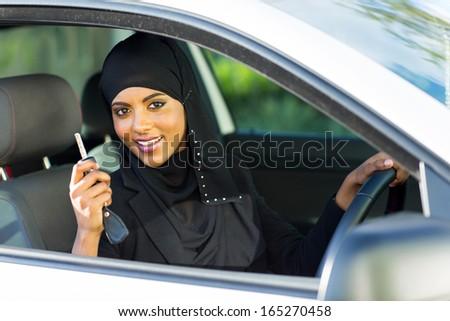 happy arabian woman holding car key inside new vehicle - stock photo
