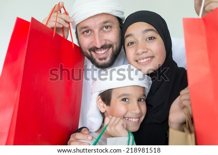 Happy Arabic family with mall shopping bags - stock photo