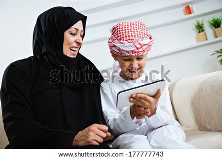Happy Arabic mother and son together sitting on the couch and using digital tablet.