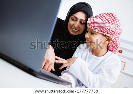 Happy Arabic mother and son together sitting on the couch and using laptop. - stock photo