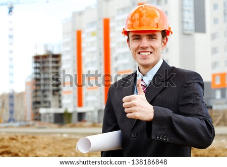 Happy architect in helmet showing sign ok over apartment building - stock photo