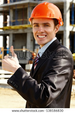 Happy architect in helmet showing sign ok while building - stock photo
