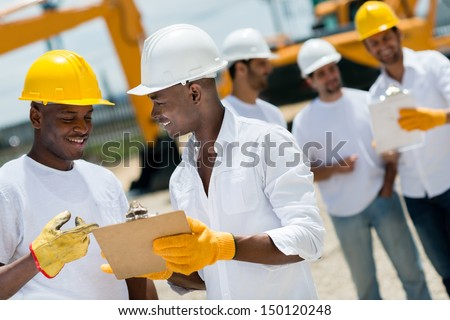 Happy architects working at a construction site outdoors  - stock photo