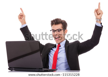 Happy arm rising winning business man at his desk working on laptop - stock photo