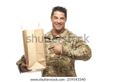 Happy Army soldier pointing at his shopping bag in front of a white background - stock photo