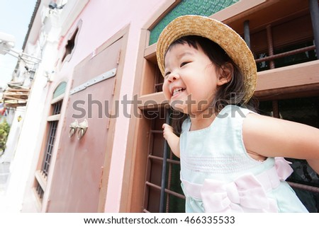 Happy asian baby girl holding the Vintage metal window on Old town street in phuket Thailand.
