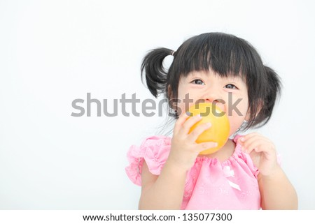 Happy Asian baby girl with Thai traditional dress holding with orange ball on white isolate