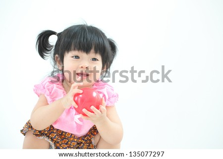 Happy Asian baby girl with Thai traditional dress playing with red ball on white isolate