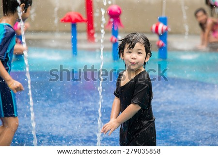 Happy asian boy has fun playing in water fountains in water park - stock photo