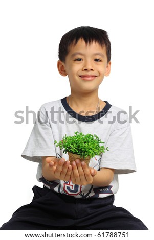 Happy Asian boy holding plant in hands. Isolated on white background.