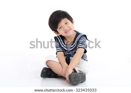 Happy asian boy in sailor uniform sitting on white background isolated