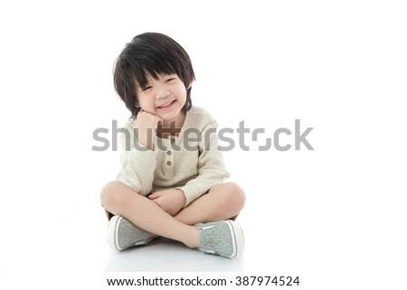 Happy asian boy sitting on white background isolated - stock photo