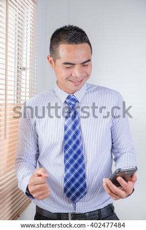 Happy asian business man looking to smart phone with happiness and cheerful