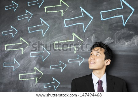 Happy Asian business man standing in front of a dark chalkboard with arrow signs drawn pointing.  - stock photo