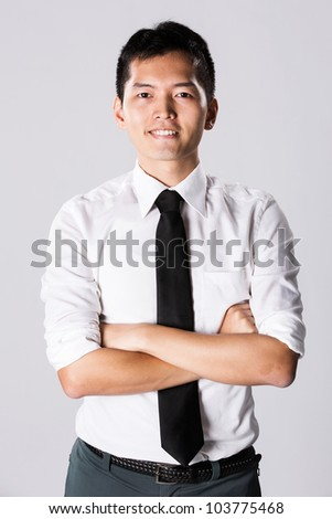 Happy Asian business man with his arms crossed.