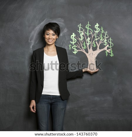 Happy Asian Business woman in front of chalk money tree drawing on blackboard. - stock photo