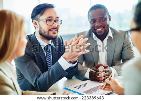 Happy Asian businessman looking at colleague during discussion