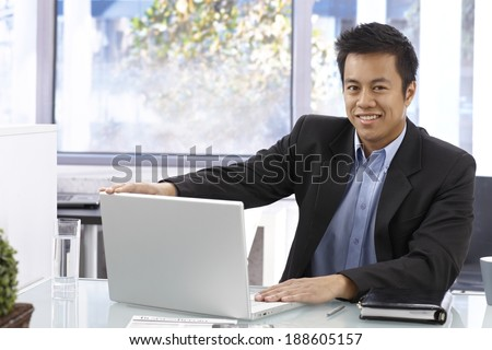 Happy Asian businessman sitting at desk, working with laptop computer, smiling, looking at camera.