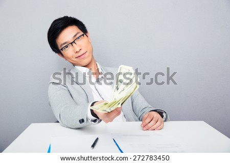 Happy asian businessman sitting at the table and holding money bills over gray background. Looking at camera - stock photo