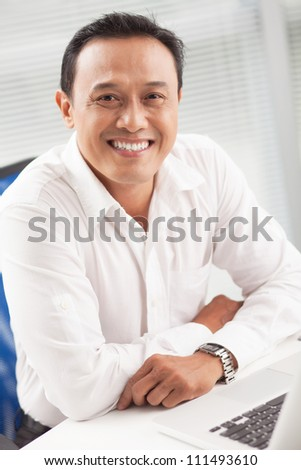 Happy Asian businessman sitting at the table and looking at camera - stock photo