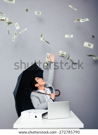 Happy asian businessman sitting at the table with umbrella with rain of money over gray background. Looking up - stock photo