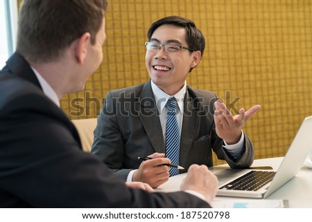 Happy Asian businessman speaking with his partner - stock photo