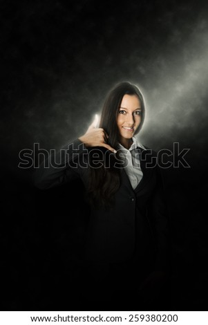 Happy Asian businesswoman giving a call me sign or gesture with her fingers in a communication concept as she stands in a beam of light - stock photo