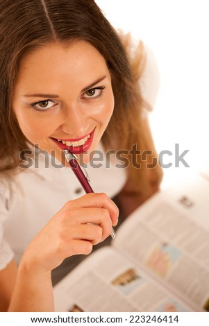Happy asian caucasian girl learning in study woth lots of books on the table isolated - stock photo