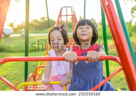 Happy Asian chidren playing swing outdor with nature light. - stock photo