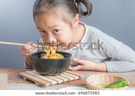 "Happy Asian child age 6 years eating Stir fried yellow noodle ""mee hokkian phuket"", small thai girl eating noodles with chopsticks in  bowl with chopsticks"