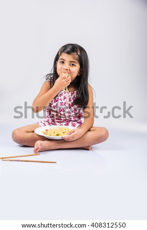 Happy Asian child eating delicious noodle, cheerful little indian girl posing with noodles in white dish isolated over white background, girl eating noodles - stock photo