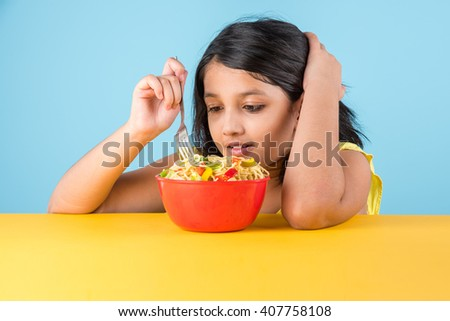 Happy Asian child eating delicious noodle, small indian girl eating noodles in red bowl, over blue background - stock photo