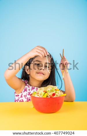 Happy Asian child eating delicious noodle, small indian girl eating noodles in red bowl with chopsticks, over blue background - stock photo