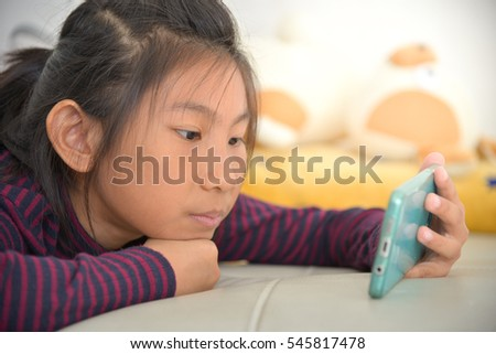 Happy Asian child girl looking at smart phone on bed at home.