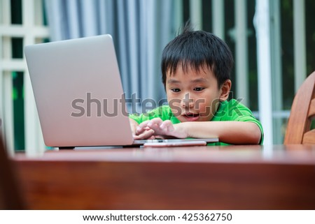 Happy asian child. Handsome boy enjoying modern generation technologies playing indoors using laptop computer and mobile phone. Education and learning concept. - stock photo