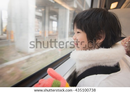 Happy asian child looking out train window outside, while it moving. travel - stock photo