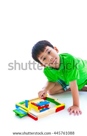 Happy asian child playing toy wood blocks, isolated on white background. Strengthen the imagination of child. Studio shot.