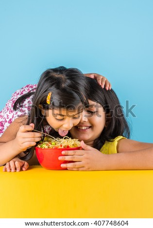 Happy Asian children eating delicious noodle, two cheerful little indian girls eating noodles in red bowl over blue background, two indian little sisters or friends with noodles - stock photo