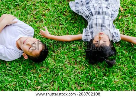 Happy Asian children lying on green grass. - stock photo