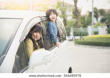 Happy asian children sitting in the car - stock photo