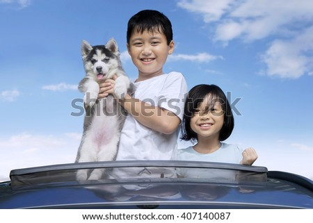 Happy Asian children standing on the sunroof of the car while holding siberian husky puppy and smiling at the camera