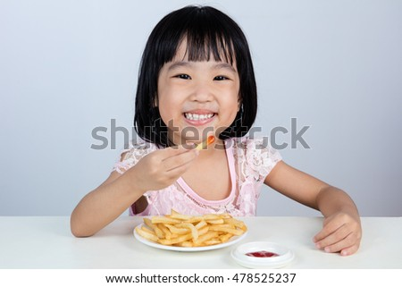 Happy Asian Chinese little girl Eating French Fries at indoor isolated clean background.