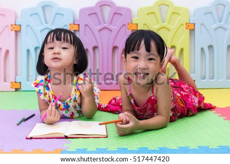 Happy Asian Chinese little sisters laying on the floor coloring at home
