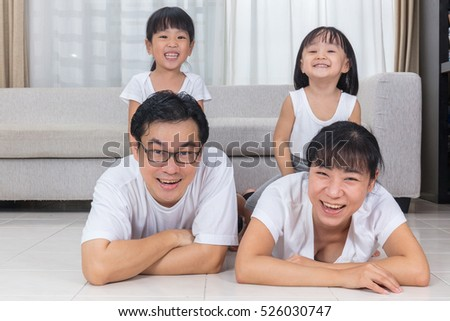 Happy Asian Chinese parents and daughters lying on the floor in the living room at home.