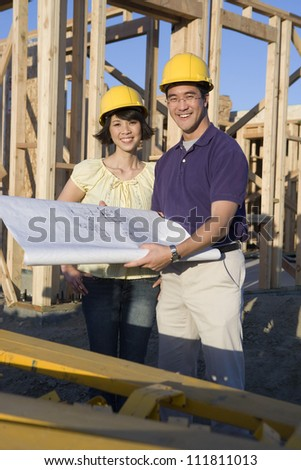 Happy asian couple at construction site