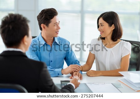 Happy Asian couple at the real estate broker office - stock photo