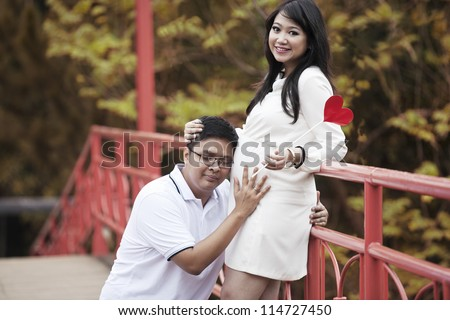 Happy Asian couple excited to see the unborn child - stock photo