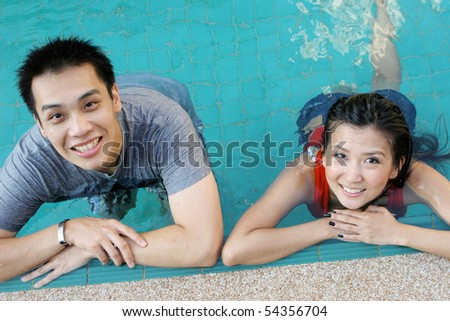 Happy Asian couple in the swimming pool on vacation. - stock photo