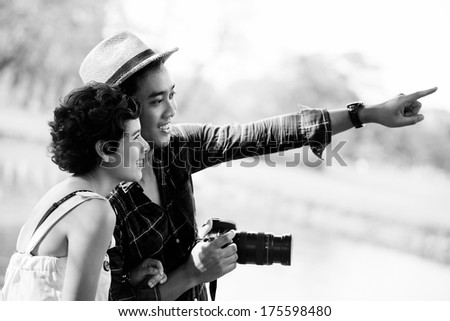 Happy asian couple tourists in nature, Black & White - stock photo